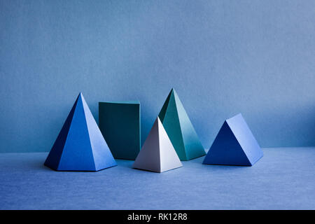 Figures géométriques encore composition de la vie. Objets rectangulaires tétraédriques de pyramide de prisme en trois dimensions sur fond bleu. Solides platoniques - image d'archive
