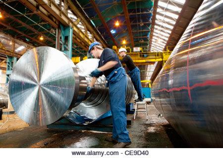 Engineer working on metal machinery - Stock Image