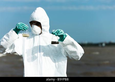 Personne en tenue de protection tenant des flacons remplis d'eau polluée - Image