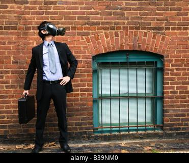 Homme d'affaires, debout à côté de mur de briques et en regardant à côté de porter un masque à gaz - Image