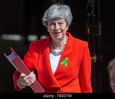Downing Street, London, UK - 15 May 2019 British Prime Minister, Theresa May, leaves Number 10 Downing Street to go to Parliament for Prime Minister's Questions. She is wearing a green badge on her lapel to raise awareness about mental illness. Credit: Tommy London/Alamy Live News - Stock Image
