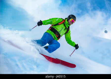 Striking shot of a colorful clothed freerider skiing the snow wave. - Stock Image