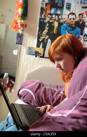 Young Women Laptop Bedroom. - Stock Image