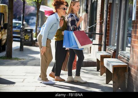 Side view of women holding shopping bags standing in street looking in shop window - Stock Image