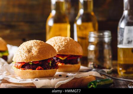 Burgers de bœuf faits maison avec des bouteilles de bière et de piment vert fort. - Image de l'éditeur