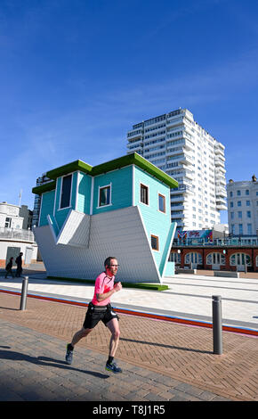 Brighton, UK. 14th May, 2019. An early morning runner passes by Brighton's newest tourist attraction the Upside Down House on the seafront near the West Pier on a beautiful sunny morning with temperatures reaching into the twenties in some parts of Britain today. The Upside Down House is due to open to the public this coming weekend . Credit: Simon Dack/Alamy Live News - Stock Image