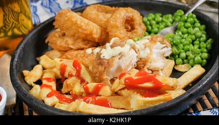 Bouchent la vue d'un anglais fish and chips avec des pois de jardin, oignons émincés et pois moelleux - Image