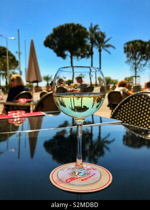 Glass of white wine on a table at a seafront restaurant in Cannes, France - Stock Image