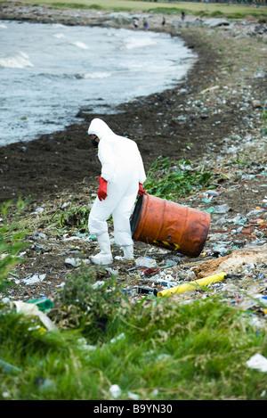 Personne en tenue de protection éliminant les déchets dangereux du paysage pollué - Image