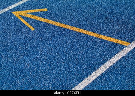 Blue tartan surface with yellow arrow - Stock Image