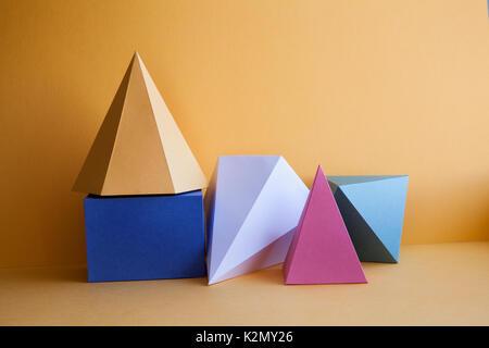 Composition de natures mortes abstraites de tissu solide platonicien. Cube rectangulaire prisme pyramide sur fond de papier jaune. Objet géométrique jaune de couleur vert blanc bleu - Image