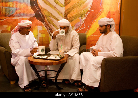 Young arab men with traditional dress sitting at starbucks cafe in Deira city centre shopping mall Dubai United Arab Emirates - Stock Image