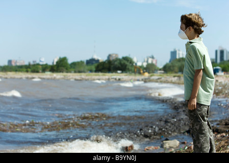 Garçon avec masque de pollution, debout sur un rivage pollué - Image