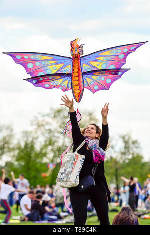 London, UK.  12 May 2019. A woman, undeterred by a lack of wind, attempts to fly a kite during the annual Streatham Kite Festival taking place on Streatham Common in South London.  Unfortunately, the large, character-style kites, that such festivals are known for, were unable to get airborne due to the wind conditions. Credit: Stephen Chung / Alamy Live News - Stock Image