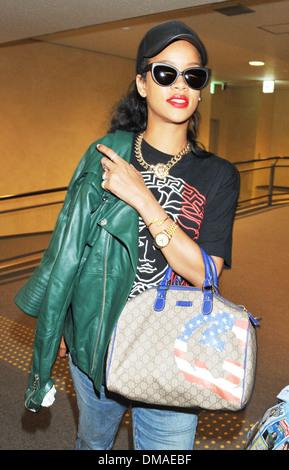 Rihanna arrives at Narita International Airport wearing a Palace 'Versace' t-shirt and carrying a Gucci handbag ahead of her - Stock Image