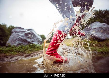 Woman splashing in muddy puddles - Stock Image