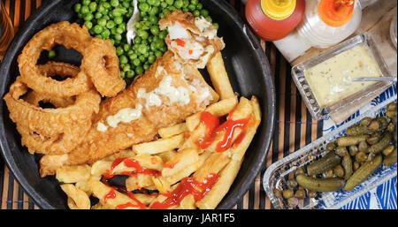 Top down vue d'un anglais fish and chips avec des pois de jardin, oignons émincés et sauce tartare - Image
