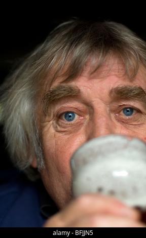 homme âgé moyen avec de longs cheveux, boire une pinte de bière - Image