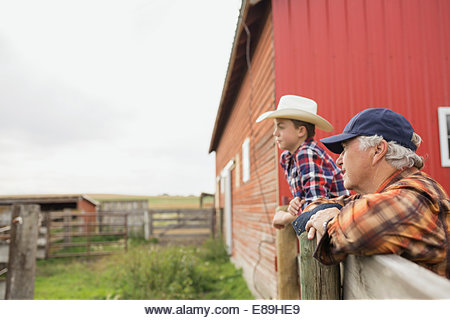 Grandfather and grandson leaning on fence on farm - Stock Image