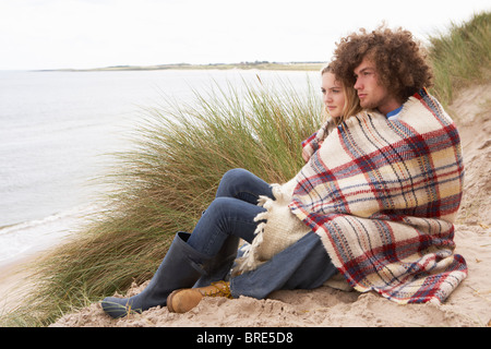Teenage Couple Sitting In Sand Dunes Wrapped In Blanket - Stock Image