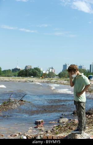 Garçon debout sur un rivage pollué, portant un masque de pollution, tête en bas - Image