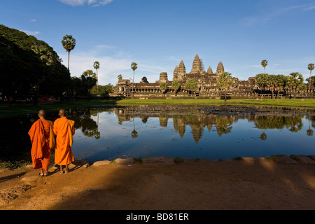 Classic view of Angkor Wat across the pools with a clear reflection, with two orange-robed monks in the foreground - Stock Image