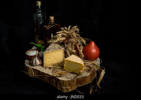 Fromage fait maison Kraft sur le fond sombre avec des légumes avec des bouteilles sur la table en bois - Image