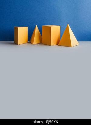 Objets rectangulaires de tétraèdre pyramidal en trois dimensions sur fond gris bleu. Figures géométriques abstraites. Couleur jaune Fond platine nature morte. espace de copie - image d'archive