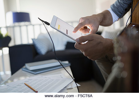 Man with guitar recording music with digital tablet - Stock Image