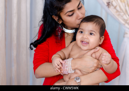 Indian mother kissing her baby girl, indoor - Stock Image