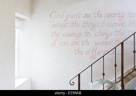 Quote on wall of rustic house - Stock Image