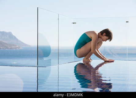 Woman crouching over infinity pool with ocean view - Stock Image