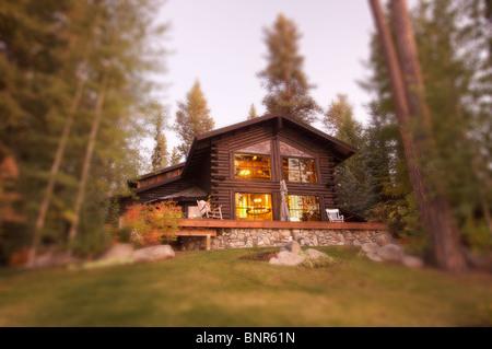 Beautiful Log Cabin Exterior Among Pine Trees - Stock Image