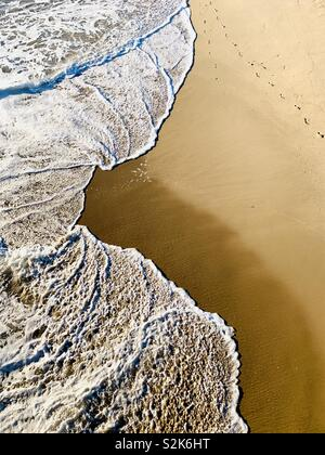 Footprints in the sand at the shoreline. Manhattan Beach, California USA - Stock Image