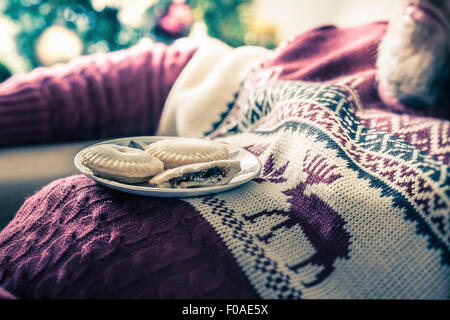 Man wearing sweater asleep with mince pies on chest - Stock Image