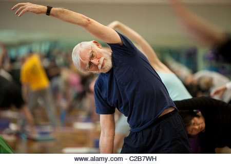A side stretch pose in a yoga class. - Stock Image
