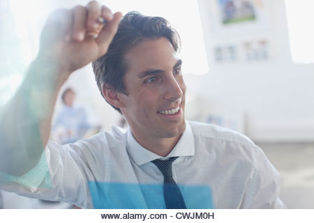 Smiling businessman leaning against glass in office - Stock Image