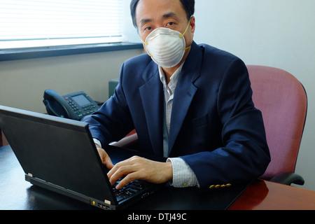 Homme asiatique portant un masque à l'intérieur du bureau en raison de la pollution de l'air - Image