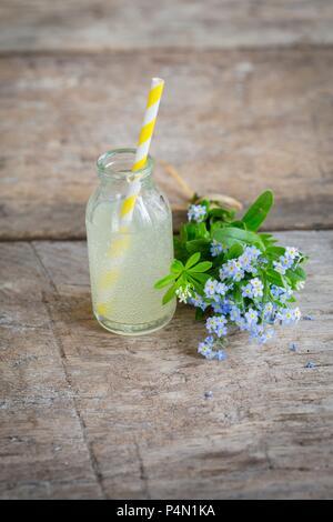 Limonade à la rhubarbe dans une bouteille en verre mini à côté d'un bouquet de myosotis - Image