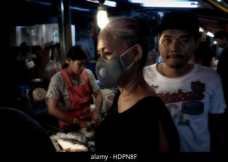 Femme portant un masque anti-pollution dans un marché de rue asiatique bondé. Thaïlande, Asie du Sud-Est - Image