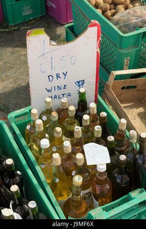 Des bouteilles de vin blanc sec à vendre dans une boîte dans un étal de marché à Marsaxlokk, à Malte. Rustique avec un signe fait maison - Image