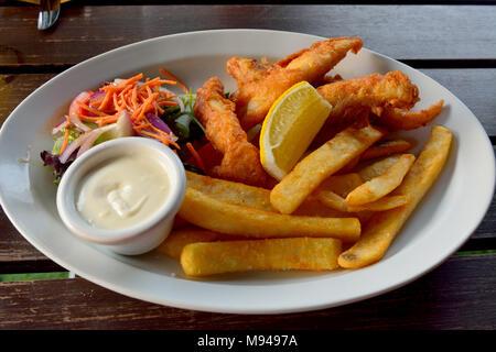Assiette de poisson-frites avec salade, sauce et citron. - Image de l'éditeur
