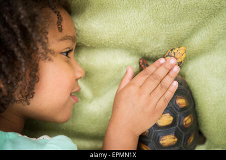 A young girl looking closely at a tortoise. - Stock Image