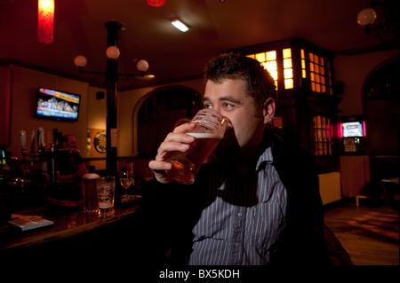 Un homme buvant une pinte de bière dans un pub, Royaume-Uni - Image