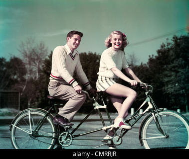 1950s SMILING  COUPLE RIDING TANDEM BICYCLE BUILT FOR TWO - Stock Image