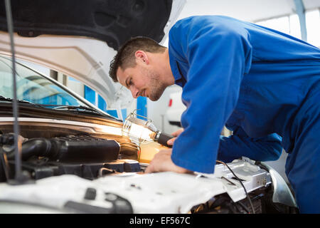 Mechanic examining under hood of car with torch - Stock Image
