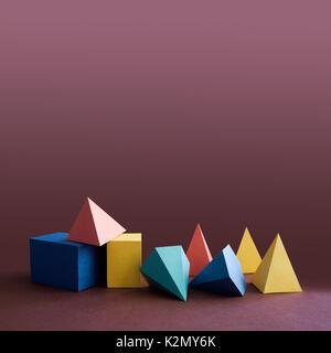 Solides platoniques colorés, figures géométriques abstraites sur fond violet. Pyramid prism cube rectangulaire jaune bleu rose vert formes colorées. Faible profondeur de champ, espace copie. - image d'archive