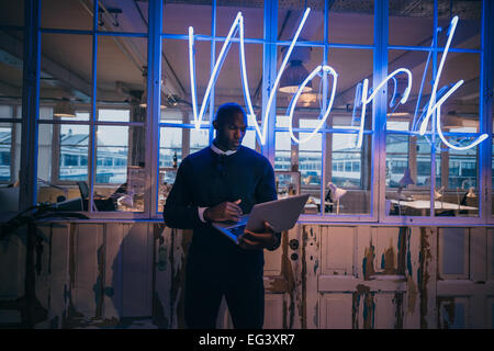 African young man standing in office using laptop computer. Business executive in office with big neon light work - Stock Image