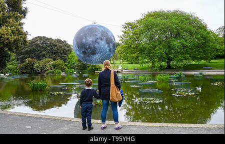 Brighton UK 30th April 2019 - A large model of the moon rises above Queens Park pond in Brighton this morning ready for tonights Brighton Festival event 'Museum of the Moon' by Luke Jerram . The moon will be lit up tonight and over the weekend accompanied by music by composer Dan Jones as it celebrates 50 years since the famous moon landing. Credit: Simon Dack / Alamy Live News - Stock Image