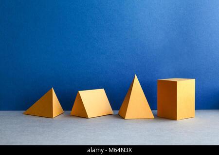 Figures géométriques abstraites. Objets rectangulaires de tétraèdre pyramidal en trois dimensions sur fond gris bleu. - image d'archive
